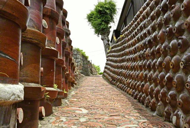 愛知県常滑市のやきもの散歩道にある土管坂。明治期の土管と昭和初期の焼酎瓶で壁面が埋め尽くされ、歴史を感じる坂道となっている=中部支社