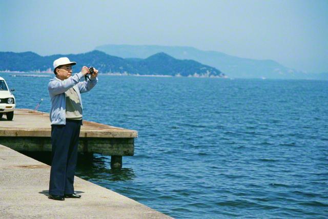 四国研修道場前の桟橋で、雄大な自然との対話をカメラに収める池田先生(1985年4月)。先生は、記念の会合に集った友へ「何ものも恐れず、どこまでも堂々と信念の道を」と語った