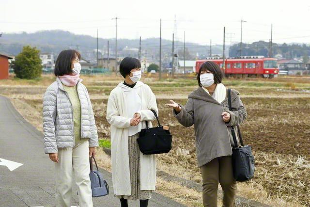 梅本智代さん㊥が小川あゆみさん㊨らと朗らかに。広布と人生の舞台は、愛知県犬山市。のどかな田園風景の中を赤い名鉄電車が走っていく(今月5日)