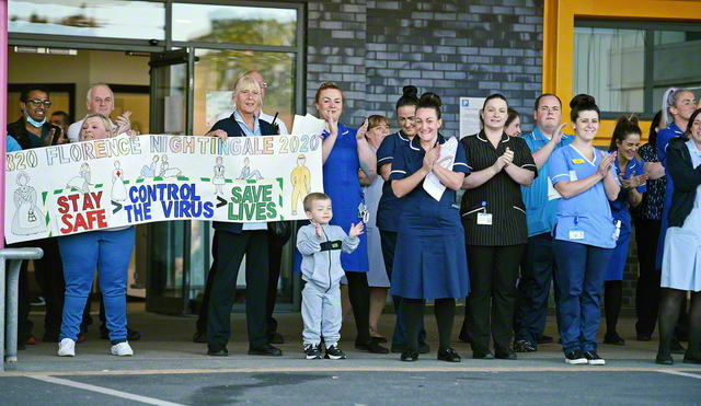 新型コロナの感染拡大が続く中、最前線で働く人々への感謝の思いを伝えるために、イギリス各地で行われた「医療・介護従事者に拍手を」のキャンペーン(昨年5月、リバプールで。AFP=時事)