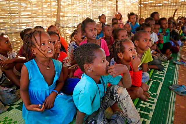 アフリカのエチオピアで激化する紛争の影響で、隣国のスーダンに逃れた難民の子どもたち。学習の機会を失わないために、難民キャンプ内で授業が行われた(昨年11月、スーダンで。AFP=時事)