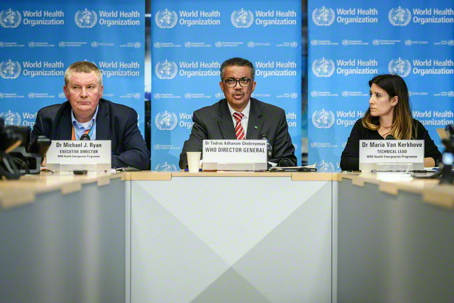 昨年3月11日、スイスのジュネーブにある世界保健機構(WHO)の本部で、新型コロナウイルス感染症の「パンデミック宣言」を行ったテドロス事務局長(写真中央。AFP=時事)