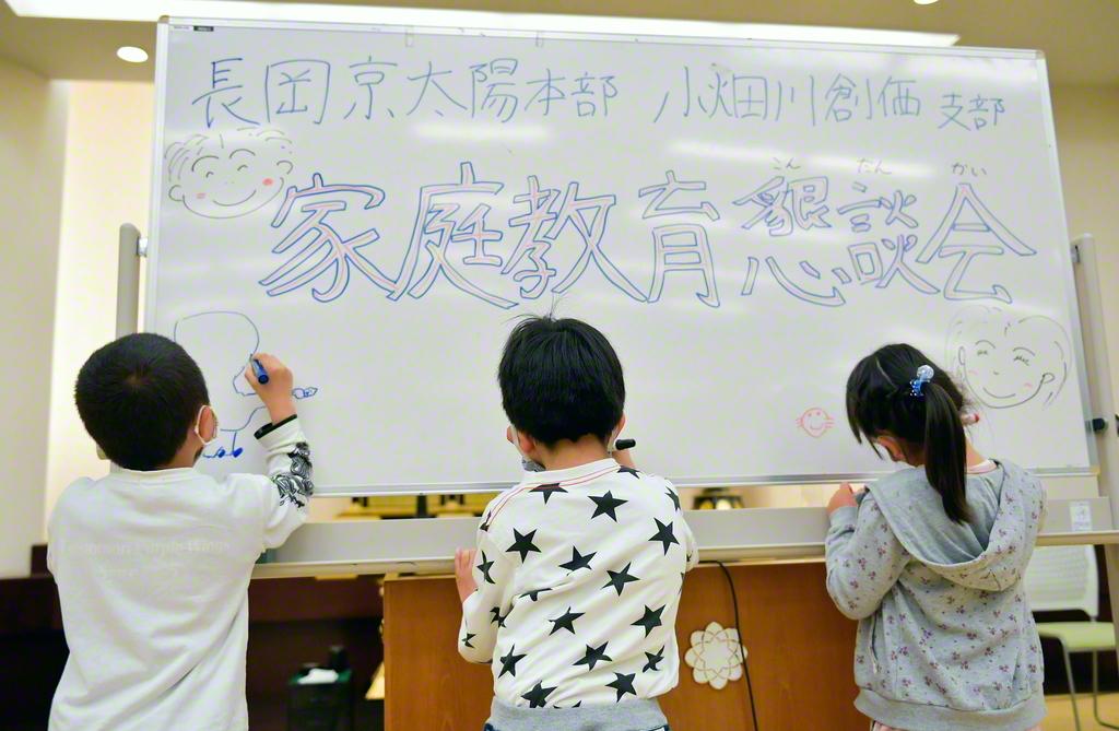 家庭教育懇談会の会場に置かれたホワイトボードに、自由に絵を描く子どもたち(今月4日、長岡京文化会館で)