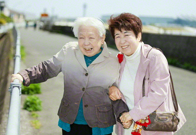 優しく手を握り、しっかり腕も組む鈴木さん㊨。いつもの散歩道を実母のミチ子さんと