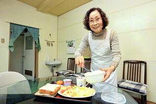 アパートの食堂で慣れた手つきで野菜や食パンを盛り合わせ、朝食を作る喜多川さん。毎日、笑顔で入所者とあいさつを交わす