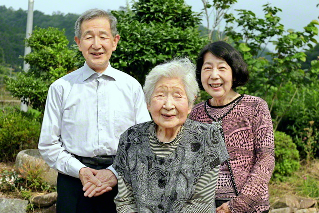 「報恩感謝の思いで地域広布に歩みます」とほほ笑む渡邉さん㊥。長男・敏弘さん㊧、順子さん夫妻と