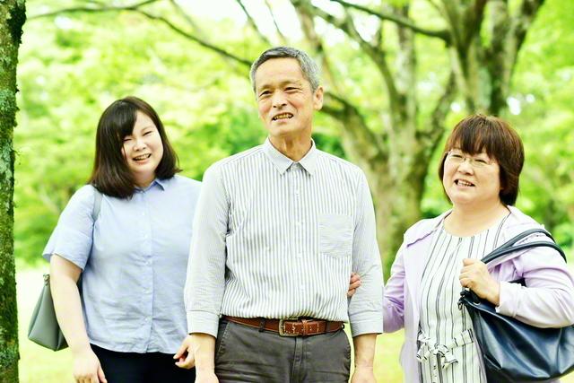 「腕を組むのなんて何年ぶりかな(笑い)。これも、病気になったおかげ」と照れ笑いする前田さん㊥を妻・英巳子さん㊨と長女・由美子さんが囲む