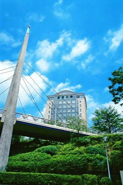 """創価大学本部棟が空に映えています。創価教育の城をつくるという""""夢のバトン""""は、牧口先生から戸田先生、そして池田先生へと受け継がれてきました。本部棟の完成は1999年5月。その2カ月後に東京・八王子市のキャンパスを訪れた池田先生が「新世紀橋」を仰ぎつつ撮影した一枚です"""