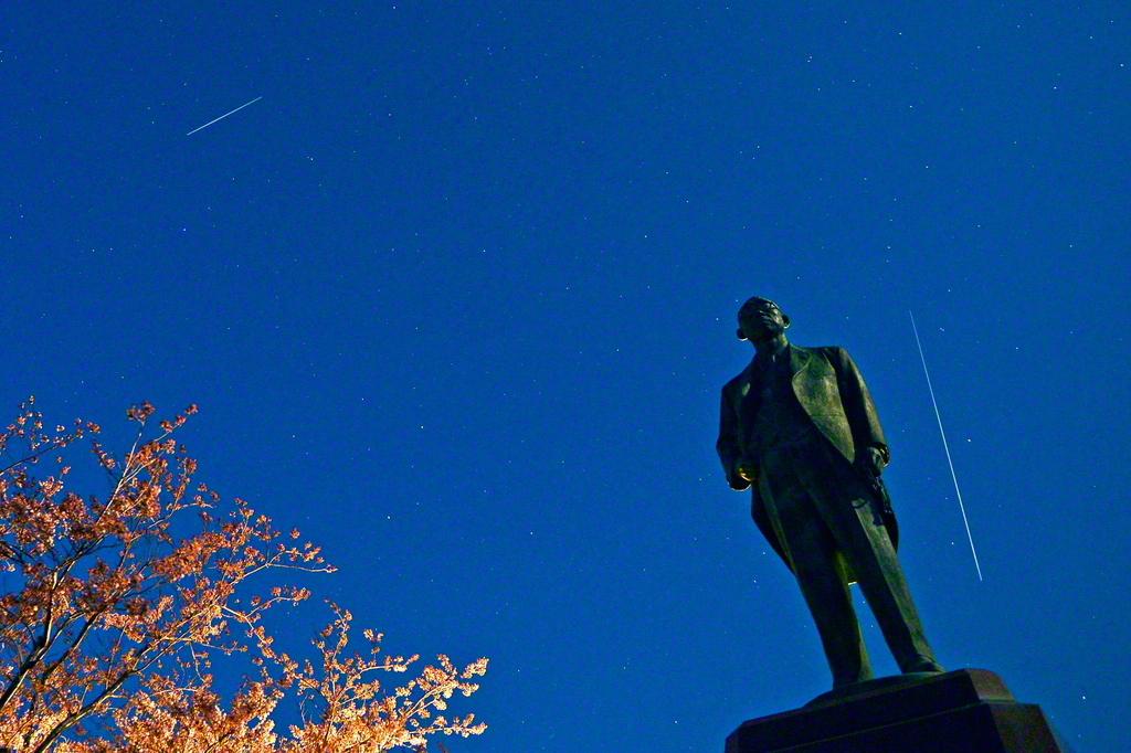 戸田先生の立像。5月5日「創価学会後継者の日」の夜空に流星の光跡が走る(写真2枚を合成)