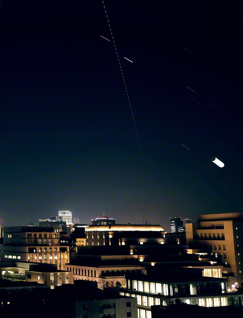 総本部の上空に国際宇宙ステーションの光跡が伸びる(18日午後6時19分=インターバル撮影し比較明合成)